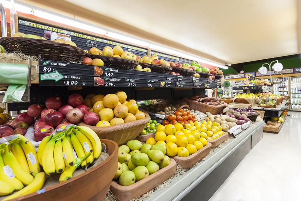 view of supermarket fresh food aisle with fruit on display